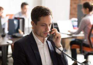 Businessman on desk phone worried
